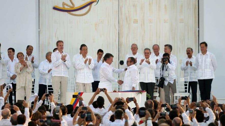 El presidente Juan Manuel Santos, izquierdo y central, estrecha la mano del máximo comandante de las Fuerzas Armadas Revolucionarias de Colombia (FARC), Rodrigo Londoño, conocido por el alias Timochenko, después de firmar un acuerdo de paz entre el gobierno y las FARC, para poner fin a más de 50 años de conflicto, en Cartagena, Colombia. AP