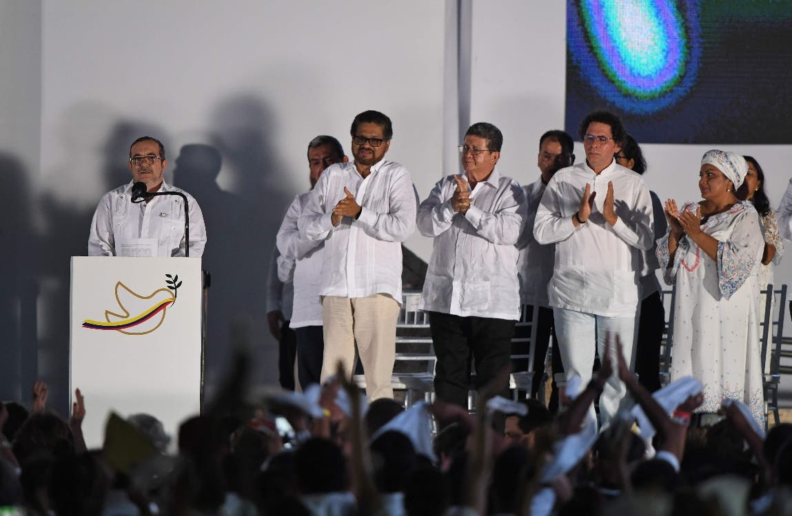 "The leader of the FARC, Rodrigo Londono (L) -- better known by his nom de guerre, Timoleon ""Timochenko"" Jimenez delivers a speech after signing the historic peace agreement between the Colombian government and the Revolutionary Armed Forces of Colombia (FARC), in Cartagena, Colombia, on September 26, 2016  The Colombian government and the leftist FARC rebel force signed a historic peace accord to end a half-century conflict that has killed hundreds of thousands of people. Santos and ""Timochenko"" Jimenez, signed the deal at a ceremony in the Caribbean city of Cartagena, prompting loud cheers from the crowd which included numerous international dignitaries.  / AFP / Luis ACOSTA"