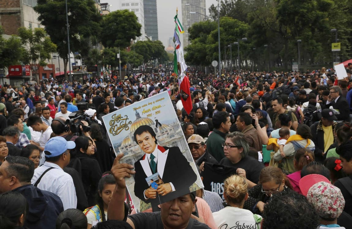 Fans stand in the street outside the Palace of Fine Arts to pay their respects to singer and songwriter Juan Gabriel, in Mexico City, Monday, Sept. 5, 2016. The singer's ashes will be on display for two days to give family, friends, and thousands of fans the opportunity to pay tribute and say goodbye. (AP Photo/Marco Ugarte)