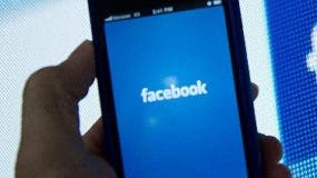 (FILES) A view of and Apple iPhone displaying the Facebook app's splash screen in front of the login page May 10, 2012 in Washington, DC. Facebook will become part of the Nasdaq 100 index of the largest non-financial companies listed on the electronic exchange, the market operator said December 5, 2012. Facebook will join the index on December 12, a statement from Nasdaq said. It will replace the IT firm Infosys, which is moving to the New York Stock Exchange. AFP PHOTO / Karen BLEIER /FILES