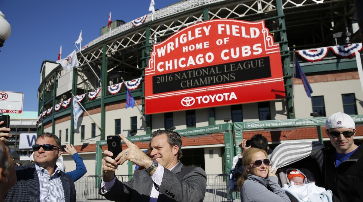 Fans take photographs under the marquee at Wrigley Field Monday, Oct. 24, 2016, in Chicago. Game 1 of the World Series between the Chicago Cubs and Cleveland Indians is Tuesday, Oct. 25 in Cleveland. (Michael Tercha/Chicago Tribune via AP)