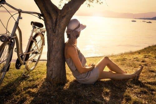 mujer-solitaria-sentada-en-el-suelo-mirando-al-lago-500x334