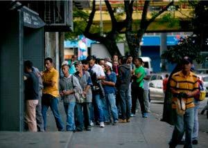 Venezolanos hacen fila para comprar pan en una panadería de Caracas.