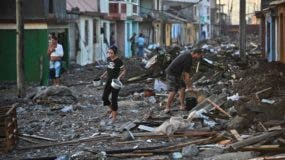 Inhabitants of Baracoa, Guantanamo province, east of Cuba clean up after hurricane Matthew passed through the place on October 7, 2016.  Hurricane Matthew moved toward Florida's east coast Friday after leaving a trail of destruction in Haiti, Cuba and the Dominican Republic. / AFP / YAMIL LAGE
