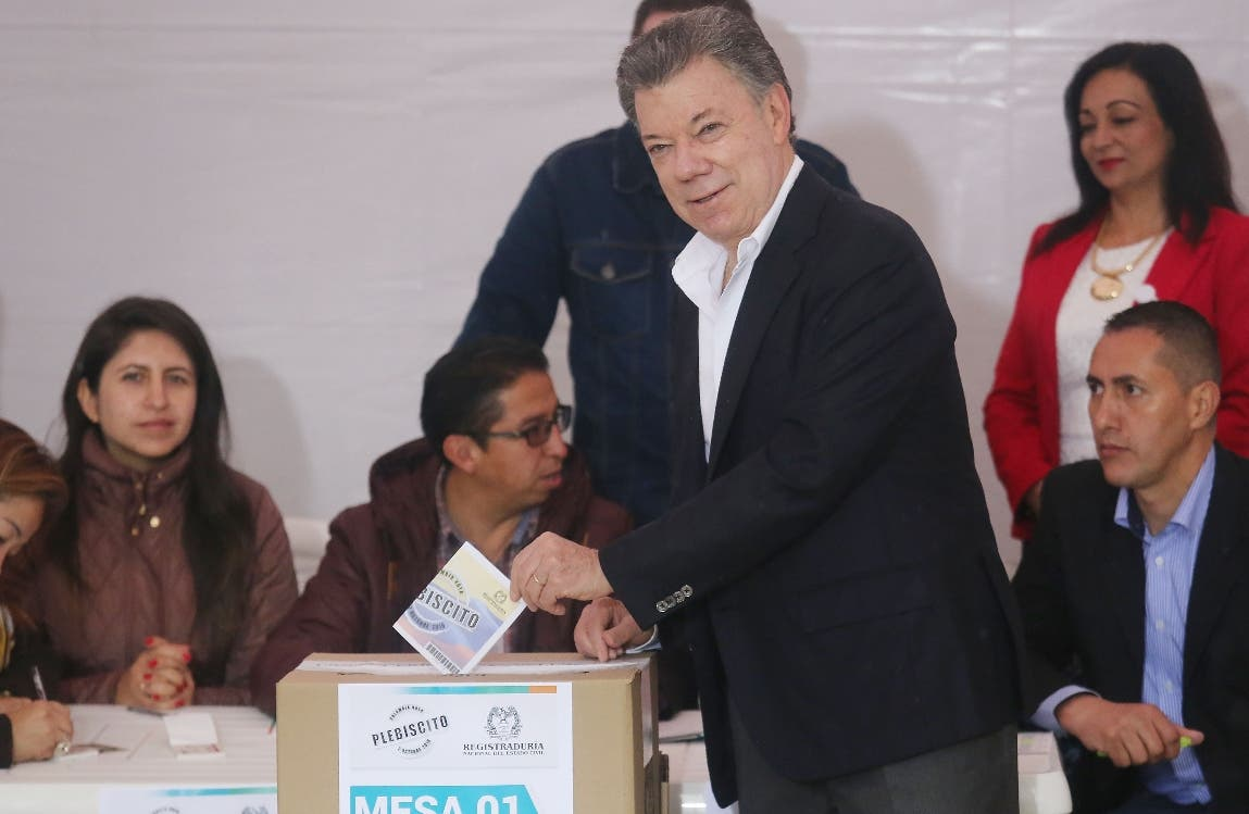 BOGOTA, COLOMBIA - OCTOBER 02: Colombia's President Juan Manuel Santos (C) casts his ballot in the referendum on a peace accord to end the 52-year-old guerrilla war between the FARC and the state on October 2, 2016 in Bogota, Colombia. The guerrilla war is the longest-running armed conflict in the Americas and has left 220,000 dead. The plan calls for a disarmament and re-integration of most of the estimated 7,000 FARC fighters.   Mario Tama/Getty Images/AFP == FOR NEWSPAPERS, INTERNET, TELCOS & TELEVISION USE ONLY ==