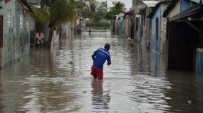A man walks in a flooded street, in a neighbourhood of the commune of Cite Soleil, in the Haitian Capital Port-au-Prince, on October 4, 2016.  Hurricane Matthew slammed into Haiti, triggering floods and forcing thousands to flee the path of a storm that has already claimed three lives in the poorest country in the Americas. / AFP / HECTOR RETAMAL