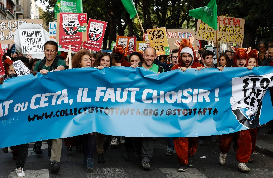 People hold a banner and placars during a demonstration for the protection of agriculture and against the Tafta and Ceta trade agreements on October 15, 2016 in Paris. Several hundred people demonstrated on October 15, 2016 afternoon in Paris to denounce the Ceta, the free trade agreement between EU and Canada, to be signed on October 27. Protesters were also mobilized against the Tafta (or TTIP), the free trade agreement project with the United States, whose scope is much larger but whose conclusion is no longer considered for this year. / AFP / FRANCOIS GUILLOT