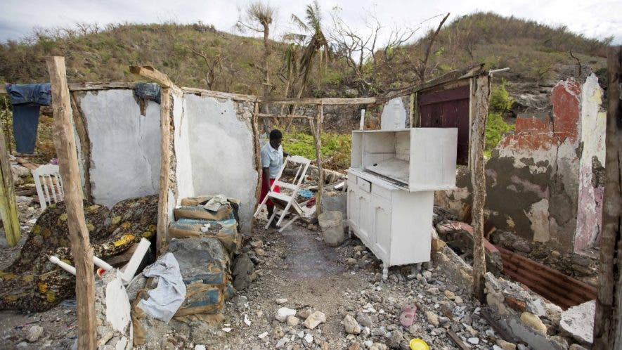 In this Wednesday, Oct. 19, 2016 photo, Mona Habraham salvages a chair from her home, destroyed by Hurricane Matthew in Port-a-Piment, a district of Les Cayes, Haiti. Family and neighbors near the town of Port-a-Piment have dug by hand through wreckage and scoured the riverbanks looking for the bodies of missing relatives, but to no avail. (AP Photo/Dieu Nalio Chery)