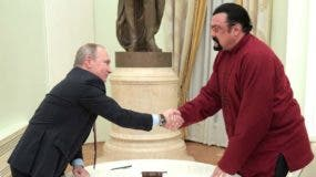 Russian President Vladimir Putin (L) shakes hands with US action hero actor Steven Seagal after presenting a Russian passport to him during a meeting at the Kremlin in Moscow on November 25, 2016. / AFP / SPUTNIK / Alexey DRUZHININ