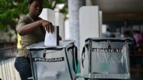 A voter casts her ballot at polling station at the Lycee National in the Petion Ville suburb of Port-au-Prince, Haiti on November 20, 2016 during the presidential and legislative elections.  Haitians go to the polls Sunday to elect a president and lawmakers, in hopes of restoring the country to constitutional order after more than a year of political crisis. Nearly 6.2 million voters are eligible to cast their ballots to choose among a vast field of 27 presidential candidates.  / AFP / HECTOR RETAMAL