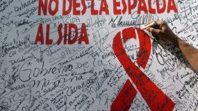REPUBLICA DOMINICANA-SIDA:EFE/ EUA CARIBE STO02- SANTO DOMINGO (REP. DOMINICANA) 01/12/05.- Un joven firma un mural de compromiso para luchar contra el VIH, durante una reunión de varias organizaciones con motivo del Día Mundial del Sida, realizado en el parque independencia de Santo Domingo. Según datos de ONUSIDA y de la OMS, el 1 por ciento de la población dominicana está afectada por el VIH/Sida, aunque esta cifra alcanza alrededor del 5 por ciento en los poblados situados entre cañaverales. EFE/Orlando Barría