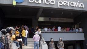 Reportaje sobre la Intervención del banco peravia, por las autoridades del estado y donde se entrevisto algunos de sus ahorrante que estaba apostado fuera de la institución bancaria. En foto :  imagen frontal banco peravia HOY  25-11-2014