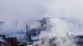 Un hombre solitario vacía un extintor de incendios sobre las ruinas ardiendo dejadas por una explosión en un mercado de fuegos artificiales que mató al menos 26 y heridas decenas.
