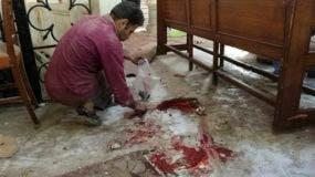 Un trabajador limpia dentro de la catedral de San Marcos en el centro de El Cairo tras un atentado el domigno 11 de diciembre de 2016. (Omar El-Hady via AP)