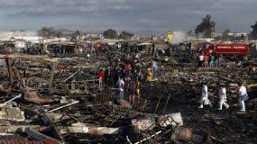 Bomberos y trabajadores de rescate caminan por el suelo quemado del mercado de fuegos artificiales más conocido de México luego de una explosión explosiva que lo atravesó, en Tultepec, México. AP