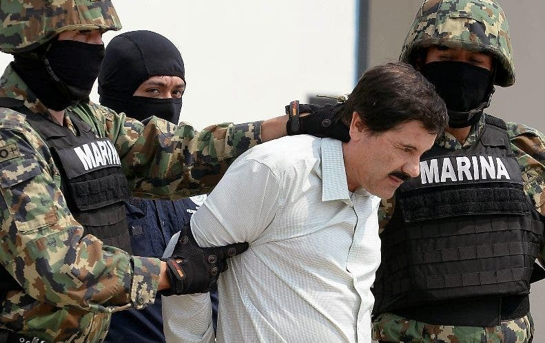"Mexican drug trafficker Joaquin Guzman Loera aka ""el Chapo Guzman"" (C), is escorted by marines as he is presented to the press on February 22, 2014 in Mexico City. The Sinaloa cartel leader - the most wanted by US and Mexican anti-drug agencies - was arrested early this morning by Mexican marines at a resort in Mazatlan, northern Mexico. AFP PHOTO/Alfredo Estrella"