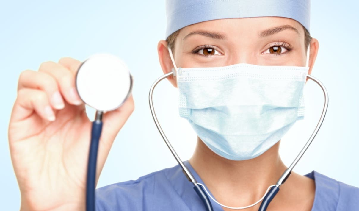 Young doctor / surgeon showing stethoscope wearing surgeon mask looking at camera. Asian / Caucasian female model.