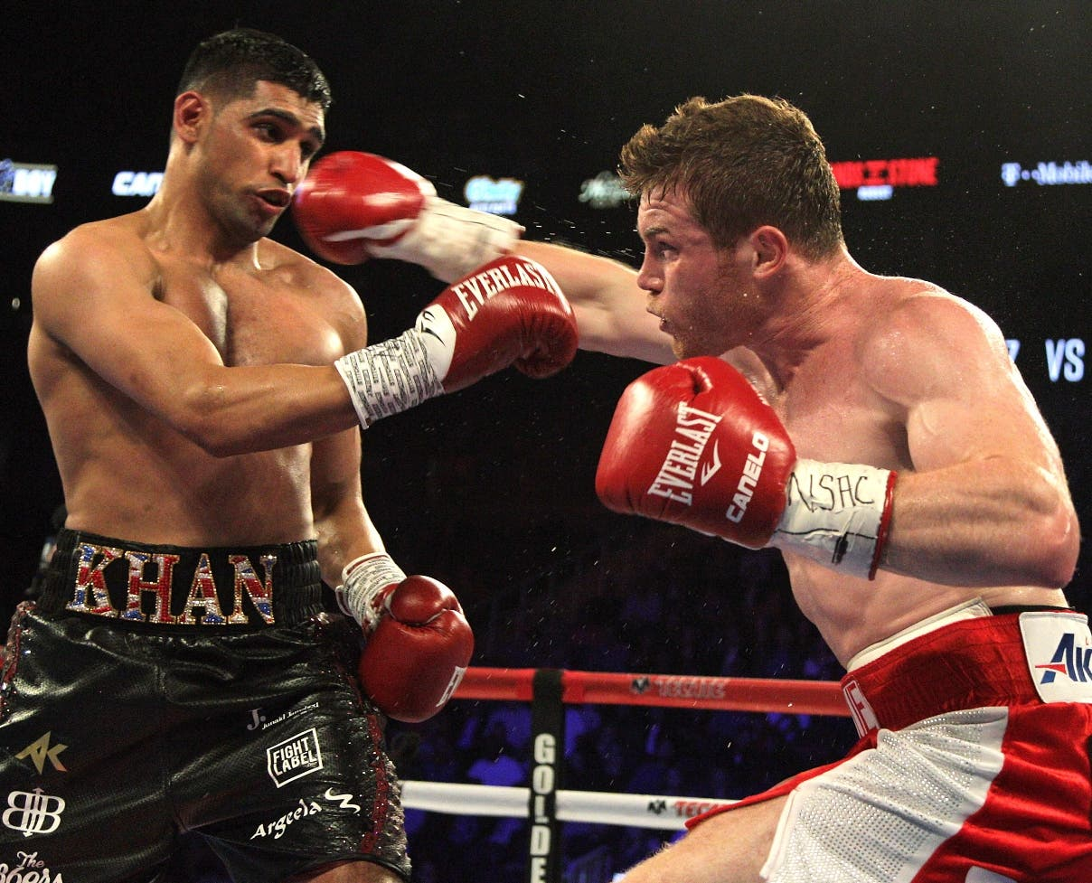 "Saul Canelo Alvarez (R) of Mexico throws a right against Amir Khan (L) of Great Britain during their WBC Middleweight Championship fight at the T-Mobile Arena, Saturday, May 7, 2016 in Las Vegas, Nevada.  Saul ""Canelo"" Alvarez successfully defended his World Boxing Council middleweight title in spectacular fashion with a devastating sixth-round knockout of Amir Khan in Las Vegas. The 25-year-old Mexican dropped Khan with a straight right hand over a left jab that sent the Briton crumbling to the canvas with just 23 seconds left in the round.   / AFP / John Gurzinski"