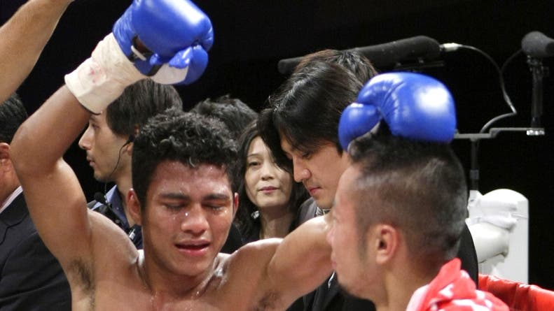 Roman Gonzalez of Nicaragua, left, and Japanese Yutaka Niida react after their WBA  Minimumweight  title match in Yokohama, Japan, Monday, Sept. 15, 2008. Gonzalez won the title, defeating Niida with a technical knockout in the 4th round . (AP Photo/Shizuo Kambayashi)