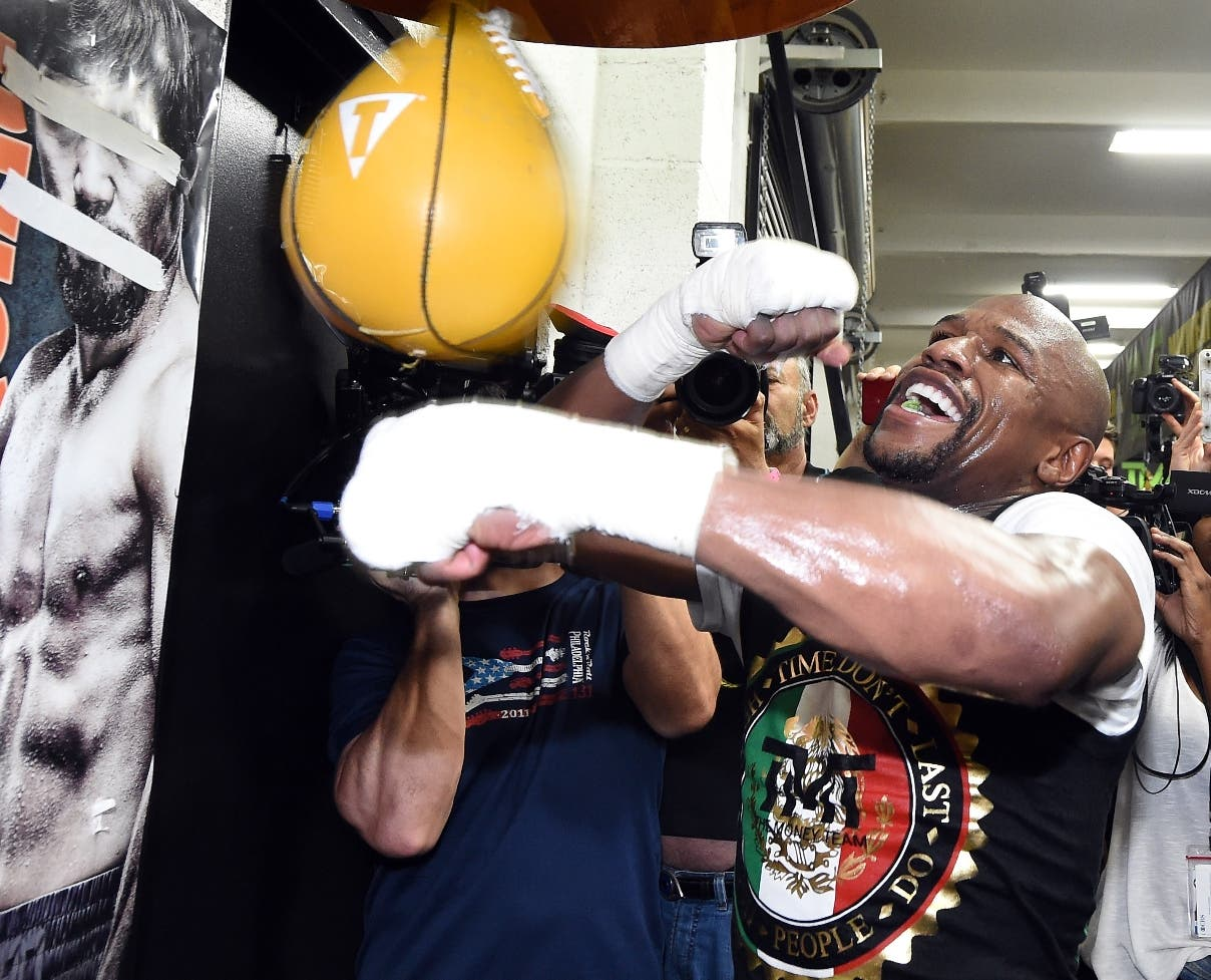 LAS VEGAS, NV - APRIL 14: WBC/WBA welterweight champion Floyd Mayweather Jr. hits a speed bag as he works out in front of a poster of WBO welterweight champion Manny Pacquiao with his eyes and mouth taped over at the Mayweather Boxing Club on April 14, 2015 in Las Vegas, Nevada. Mayweather will face Pacquiao in a unification bout on May 2, 2015 in Las Vegas.   Ethan Miller/Getty Images/AFP == FOR NEWSPAPERS, INTERNET, TELCOS & TELEVISION USE ONLY ==