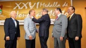 El presidente Medina entrega a Rondón la Medalla al Mérito en Ganadería, otorgada por la Asociación Dominicana de Hacendados y Agricultores (ADHA), por sus aportes al desarrollo de la producción agropecuaria nacional, en octubre de 2013.
