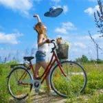 linda-chica-disfruta-un-dia-soleado-a-orillas-de-la-ciudad-con-mascota-en-la-bicicleta