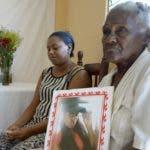 La señora Celeste Carmona,abuela de Katerin Figueroa joven asesinada,sostiene una foto de su nieta frenta al altar donde se le rinden oraciones durante 9 dias en el sector de Guachupita/foto Jose de Leon