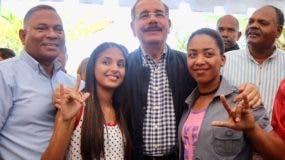 Las jóvenes dicen te quiero con sus manos junto al presidente Danilo Medina.