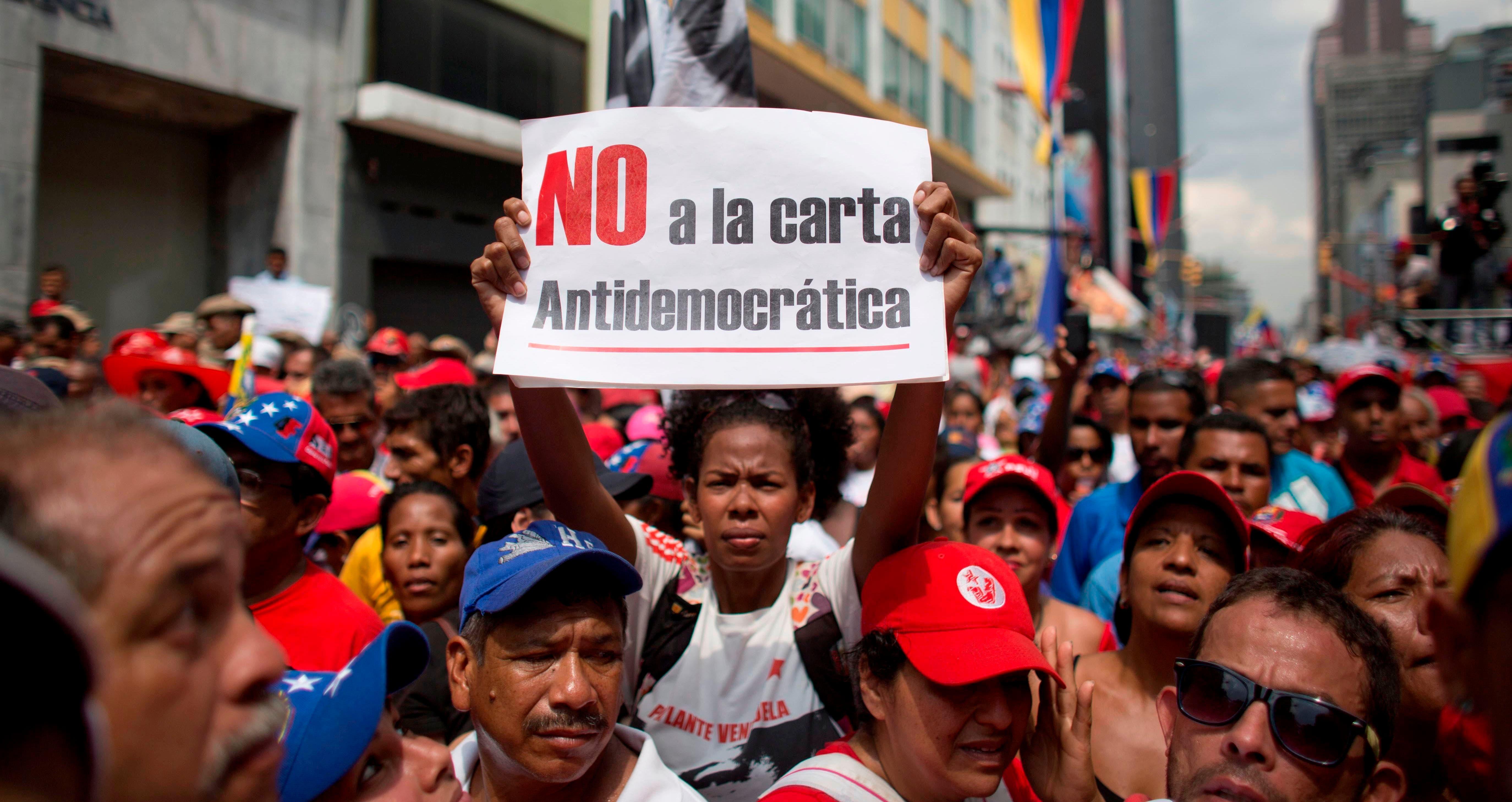 Una mujer sostiene un letrero durante una marcha en rechazo a las posibles sanciones que podría aplicar la OEA al gobierno del presidente Nicolás Maduro en Caracas, Venezuela, el martes 28 de marzo de 2017.