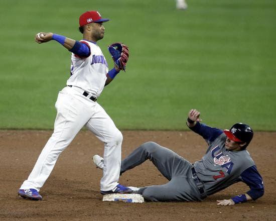 Robinson Canó (L), lanza al primer lugar como el jardinero de los Estados Unidos Christian Yelich (R) se desliza hacia la segunda base para completar el doble juego en la quinta entrada en la segunda ronda del Clásico Mundial de Béisbol en San Diego, California, EE.UU.