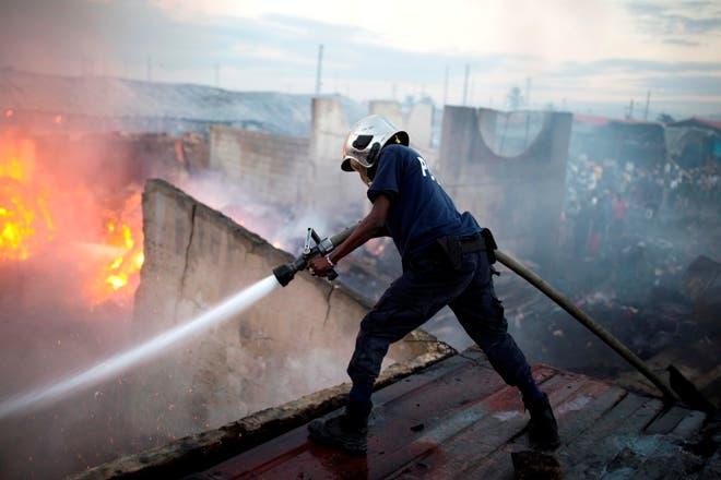 Bomberos sofocan el fuego que afectó el mercado. Foto: AP