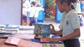 Niños y jóvenes aprecian los títulos de obras que les atraen en la Feria del Libro 2017.