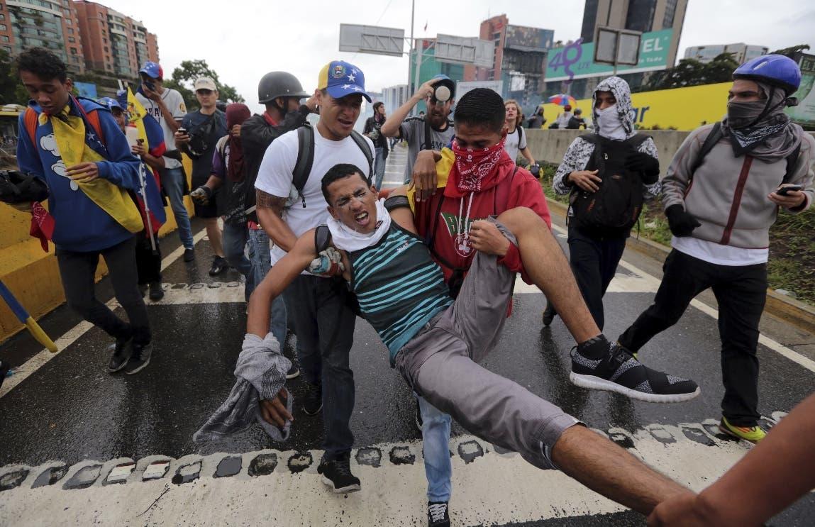 Un joven sufriendo los efectos del gas lacrimógeno es evacuado por compañeros manifestantes durante enfrentamientos entre miembros de la oposición y soldados de la Guardia Nacional Bolivariana, en Caracas, Venezuela. AP/Foto de archivo.