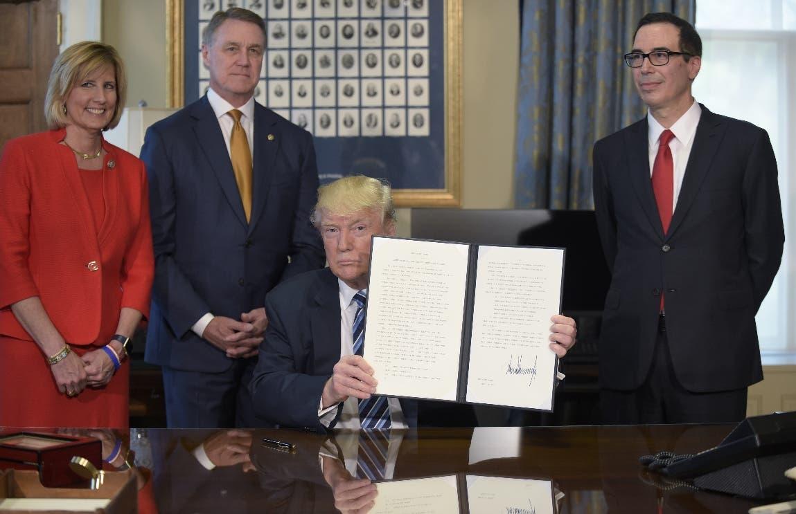 El presidente Donald Trump muestra una orden ejecutiva firmada para identificar y reducir las cargas fiscales fiscales  en el Departamento del Tesoro de Washington. Desde la izquierda están la diputada Claudia Tenney, R-N.Y., el senador David Perdue, R-Ga., Y el secretario del Tesoro, Steven Mnuchin. (Foto de AP / Susan Walsh)