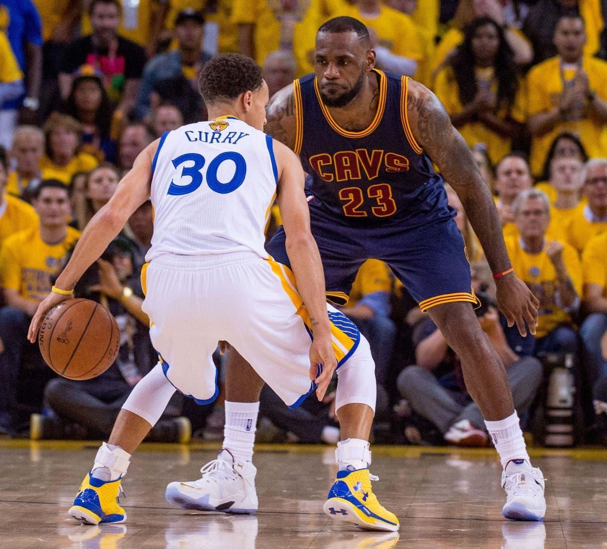 Stephen Curry, principal figura de los Warriors, marcado por el astro de los Cavs LeBron James.