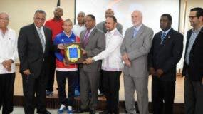 El ministro de Deportes, Danilo Díaz y el presidente del COD, Luis Mejía entregan la placa a Reyes.