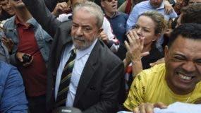 El expresidente de Brasil Luiz Inacio Lula da Silva, adelante en el centro, es ovacionado por simpatizantes al llegar al edificio federal de Justicia en Curitiba, Brasil. Lula testificó el miércoles en un caso de corrupción en contra suya, viéndose por primera vez cara a cara con el juez federal que supervisa la investigación de una extensa red de corrupción que ha creado cambios drásticos en Brasil. (AP Foto/Denis Ferreira Netto)