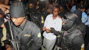 Peralta es custodiado al salir de la audiencia en la que el Ministerio Público pidió ser condenado.