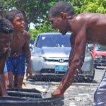 En  Guachupita, Gelson Vásquez se divertía al compartir con sus hijos un baño de agua a la intemperie con una manguera.