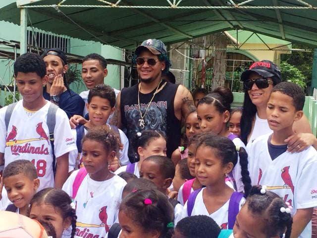 Carlos Martínez junto a varios de los niños a quienes donó útiles escolares en Puerto Plata.