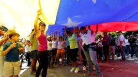 Miembros de la oposición ondean una bandera venezolana ante un centro de votación durante una consulta simbólica en Caracas, Venezuela, el domingo 16 de julio de 2017. (AP Foto/Ariana Cubillos)