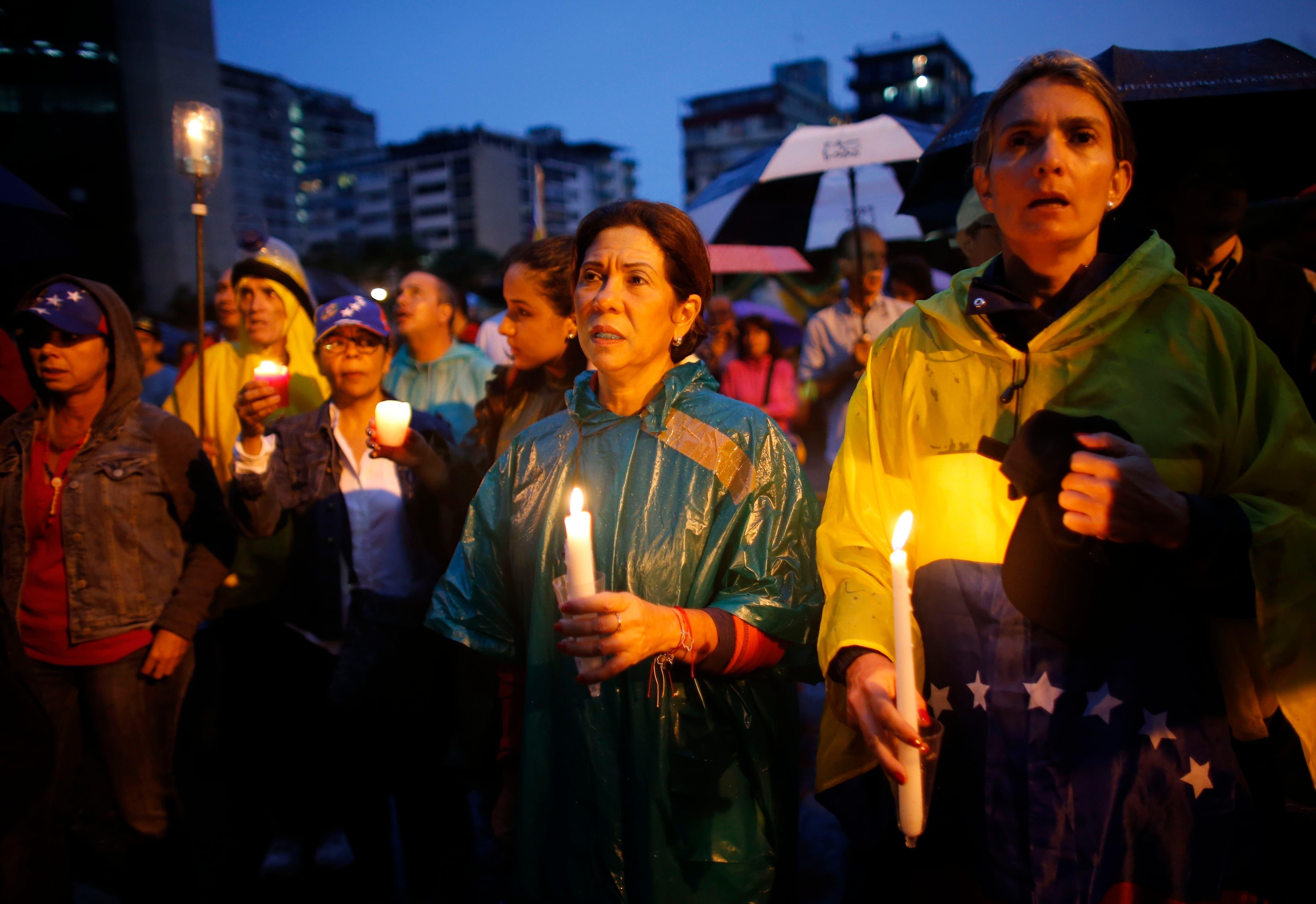 Un grupo de personas participan en una vigilia en honor de más de 90 personas que han muerto durante tres meses de protestas en contra del gobierno en Caracas,