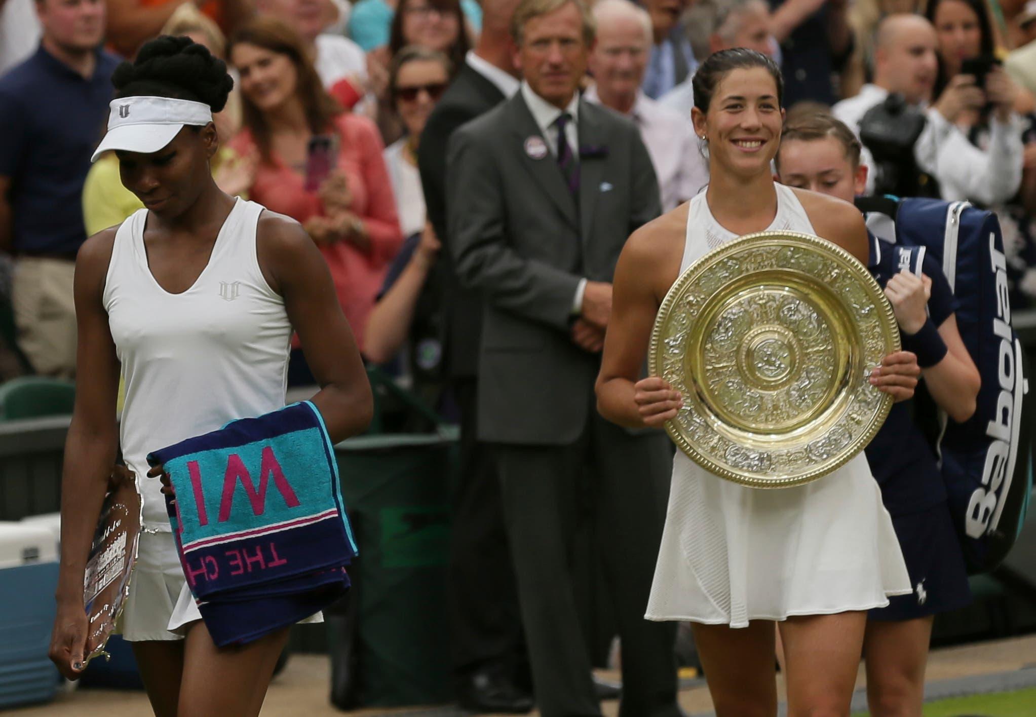 Venus Williams, de Estados Unidos, salió con su trofeo de la Corte Central después de su derrota ante la española Garbine Muguruza, a la derecha, en la final femenina de los Singles el día doce en el Wimbledon Tennis Championships de Londres el sábado 15 de julio de 2017. AP Foto / Tim Irlanda).