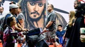 Los visitantes pasan por una foto del personaje de Disney Capitán Jack Sparrow durante la Expo D23 en el Anaheim Convention Center en Anaheim, California, el viernes 14 de julio de 2017. AP