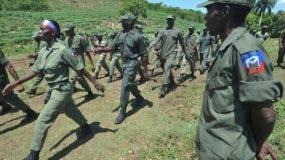 Esta foto de archivo tomada el 18 de mayo de 2013 muestra a miembros del ejército haitiano disuelto que demuestra Meyer, 15 kilómetros (10 millas) al sur de Puerto Príncipe, para demandar el restablecimiento del ejército que fue disuelto por el ex presidente Jean- Bertrand Aristide. AFP