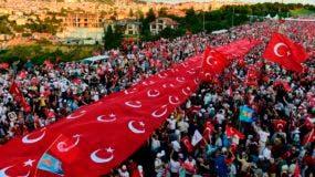 """La gente está de pie bajo una colección de banderas nacionales turcas que se reúnen en el """"Puente de los Mártires del 15 de julio"""" (Puente del Bósforo) en Estambul el 15 de julio de 2017. Turquía está marcando un año desde la derrota del golpe destinado a derrocar al Presidente Recep Tayyip Erdogan , Buscando mostrar la unidad nacional y su dominio del poder en una sociedad cada vez más polarizada. AFP"""
