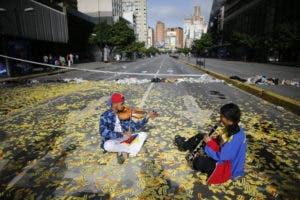 Los músicos juegan sus instrumentos mientras se sientan en medio de una carretera llena de boletos de metro en una barricada instalada por manifestantes anti-gobierno en Caracas, Venezuela. AP