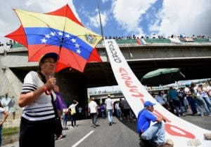 Opposition activists take part in a protest against the government of President Nicolas Maduro, at the Francisco Fajardo highway in Caracas, on July 1, 2017. Venezuela marks three months of violent protests within a political and economic crisis with protesters demanding President Nicolas Maduro's resignation and new elections.  / AFP / JUAN BARRETO