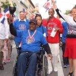 José Santos, discapacitado exatleta, porta la antorcha en desfile.
