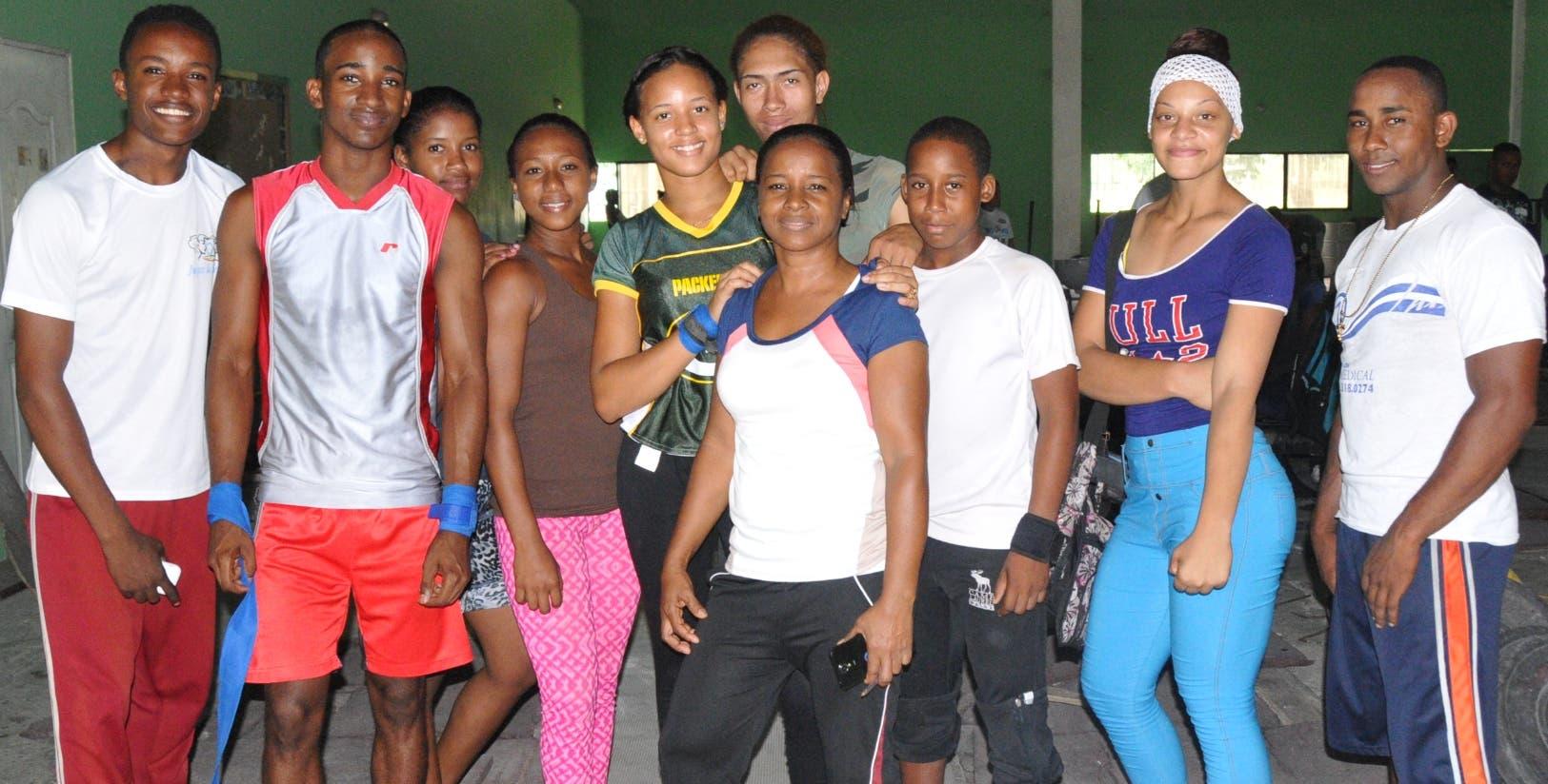 Guillermina Candelario, centro, junto a jóvenes atletas de pesas de su escuela y otros que se   entrenan en el polideportivo local.